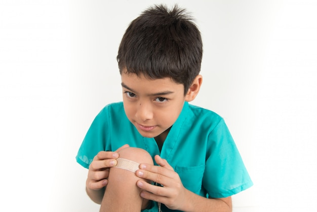 Ragazzino che utilizza un cerotto in gesso sul ginocchio Foto Premium