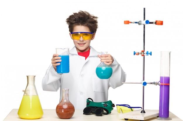 Ragazzino come chimico che fa esperimento con liquido chimico in laboratorio Foto Gratuite