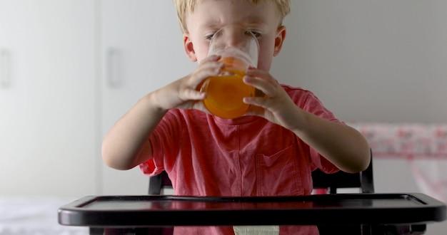 Ragazzino con arance e succo. ragazzino felice che beve il succo d'arancia a casa Foto Premium