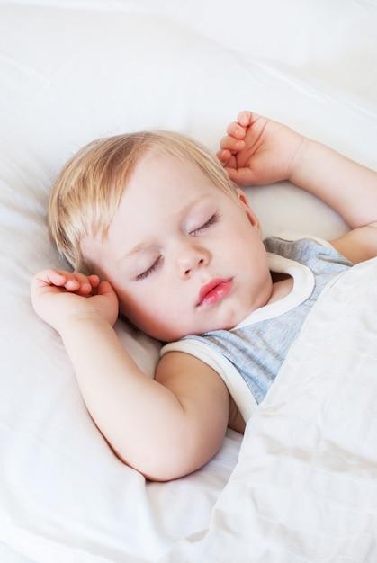 Ragazzino con capelli biondi che dorme su un letto Foto Premium