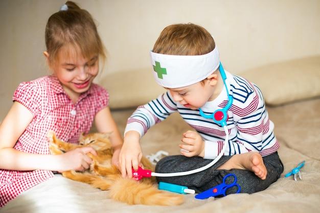 Ragazzino con gli occhiali con sindrome alba e ragazza bionda gioca con giocattoli e gatto zenzero Foto Premium
