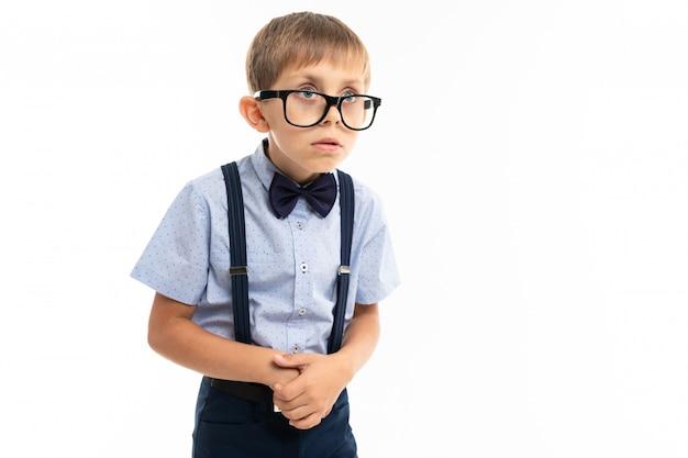 Ragazzino con gli occhiali neri con sedie trasparenti, camicia blu, pull-up molto insicuro Foto Premium