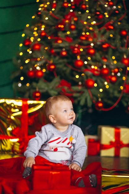 Ragazzino con i regali di natale dall'albero di chriostmas Foto Gratuite