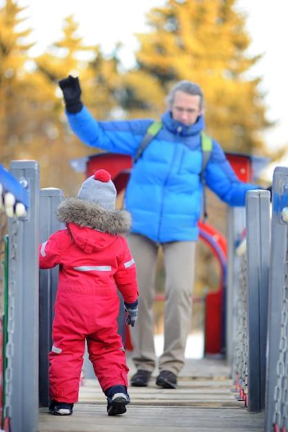 Ragazzino con suo padre / nonno divertirsi insieme nel parco invernale innevato Foto Premium