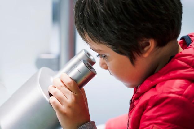Ragazzino curioso che osserva tramite il microscopio mentre divertendosi nel randello scientifico per i bambini in età prescolare Foto Premium
