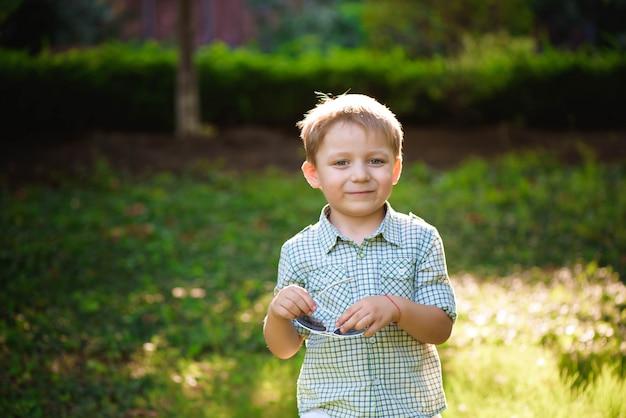Ragazzino divertente in occhiali da sole. ragazzo bambino in occhiali da sole Foto Premium
