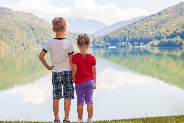 Ragazzino e ragazza che stanno tenendosi per mano sulla riva di un lago Foto Premium