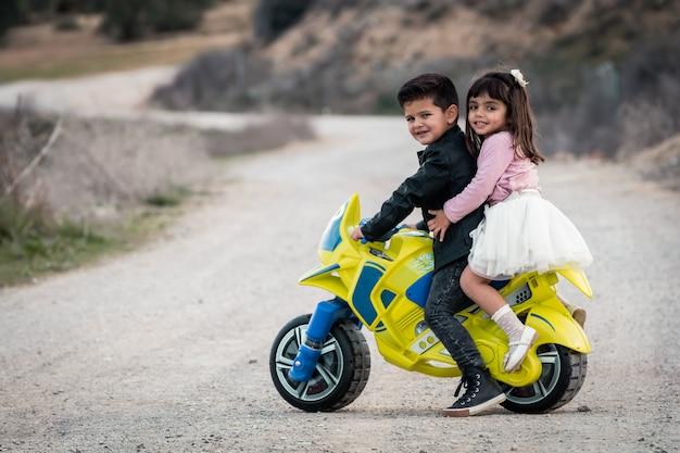 Ragazzino e ragazza in sella a moto giocattolo Foto Premium