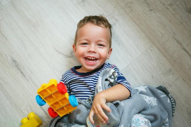 Ragazzino felice divertendosi ridendo sul pavimento - vista dall'alto Foto Premium