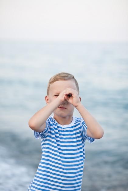 Ragazzino in maglietta a strisce che gioca sulla spiaggia con sfondo sfocato sul mare Foto Premium