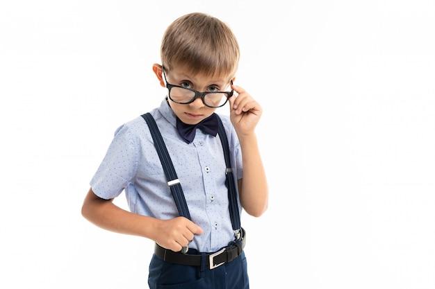 Ragazzino in occhiali neri con occhiali trasparenti, camicia blu, pull-up guarda la telecamera Foto Premium
