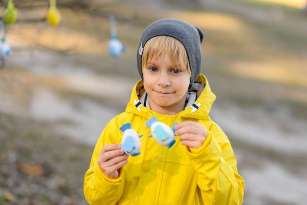 Ragazzino in un impermeabile giallo luminoso che gioca con le uova di pasqua sulla natura, concetto di pasqua Foto Premium