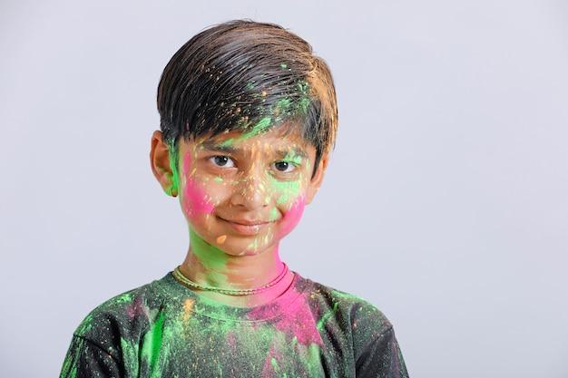 Ragazzino indiano che gioca con il colore nel festival di holi Foto Premium