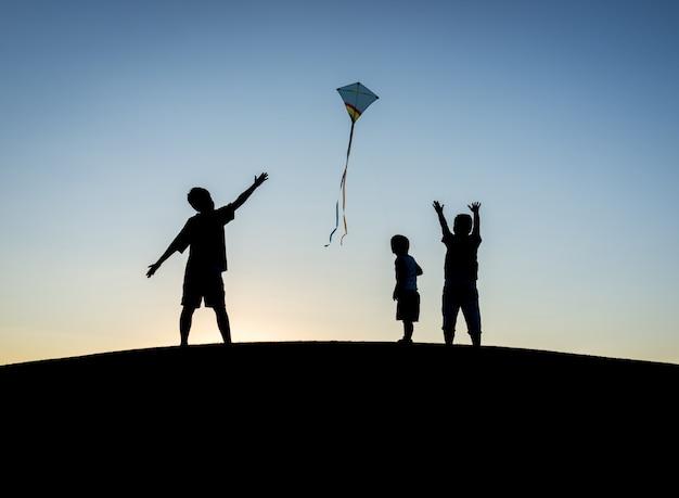 Ragazzino sulle vacanze estive divertendosi e tempo felice che pilota aquilone sulla spiaggia del mare Foto Premium