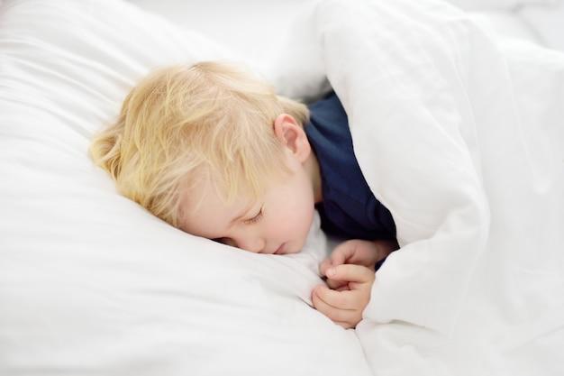 Ragazzino sveglio che dorme. bambino stanco schiacciando un pisolino nel letto dei genitori. Foto Premium