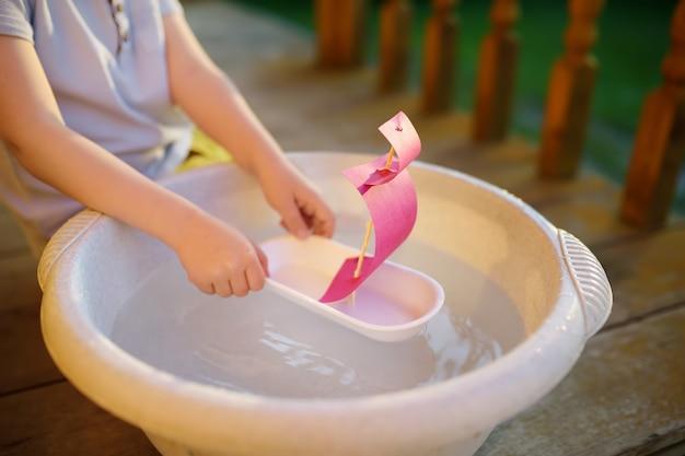 Ragazzino sveglio che gioca con la nave fatta in casa nel bacino d'acqua sotto il portico di casa. i bambini giocano. Foto Premium