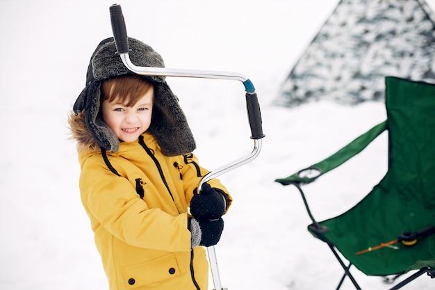 Ragazzino sveglio che si siede su una pesca invernale Foto Gratuite