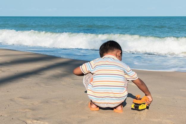 Ragazzino sveglio gioca auto giocattolo sulla spiaggia Foto Premium