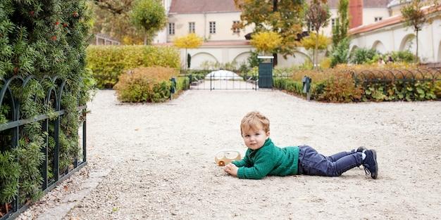 Ragazzino sveglio sorridente che si trova e che gioca sulla terra nel parco. ragazzino adorabile nel giardino di autunno. attività all'aperto per bambini. copia spazio Foto Premium
