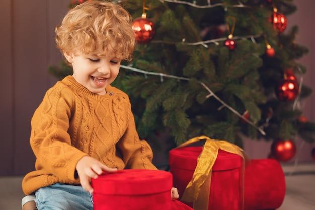 Ragazzino vicino all'albero di natale in un maglione marrone Foto Gratuite