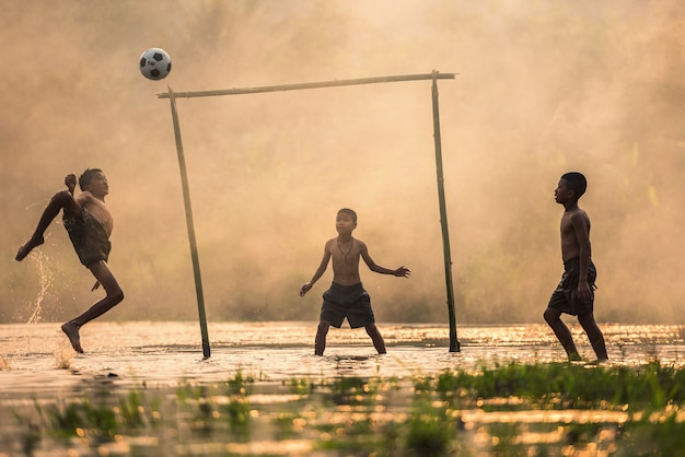 Ragazzo a calci un pallone da calcio Foto Premium