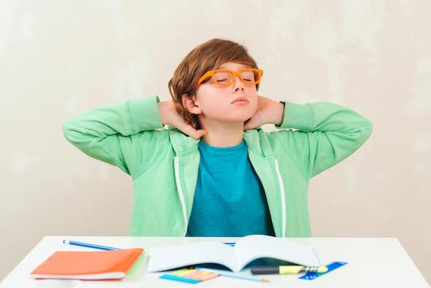 Ragazzo a fare i compiti. difficoltà di apprendimento, concetto di educazione. ragazzo stressato e stanco. Foto Premium