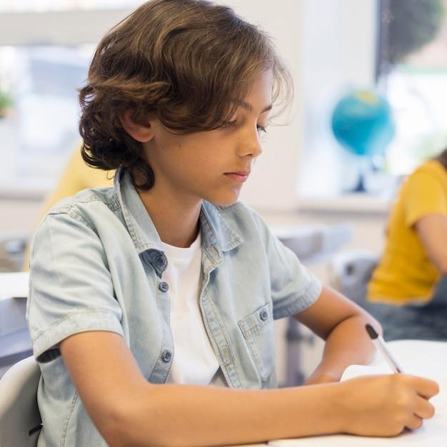 Ragazzo a scuola scrivendo Foto Gratuite