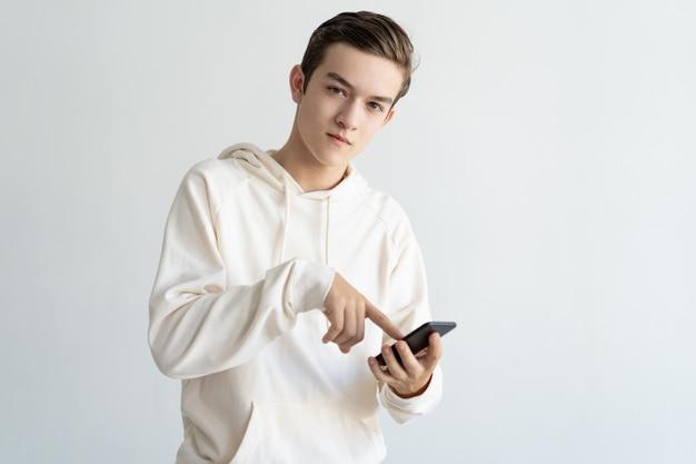 Ragazzo adolescente fiducioso pubblicità nuova app mobile Foto Gratuite
