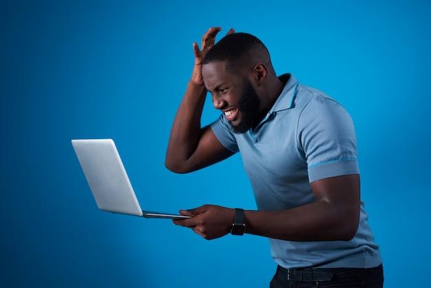 Ragazzo africano con laptop e tenendo la testa Foto Premium