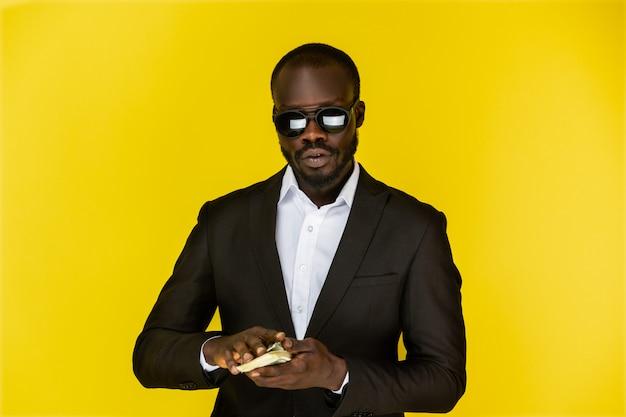 Ragazzo afroamericano tiene dollari con entrambe le mani, indossa occhiali da sole e abito nero Foto Gratuite