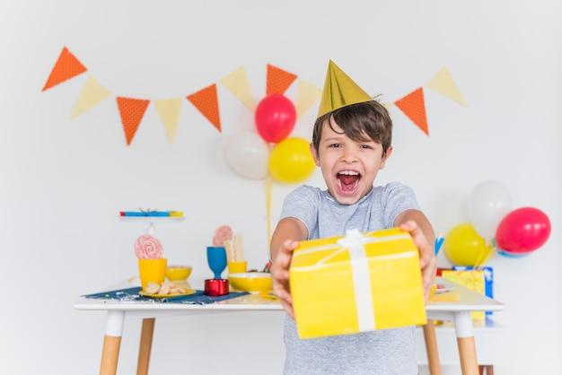 Ragazzo allegro che cattura il contenitore di regalo giallo con il nastro bianco Foto Gratuite