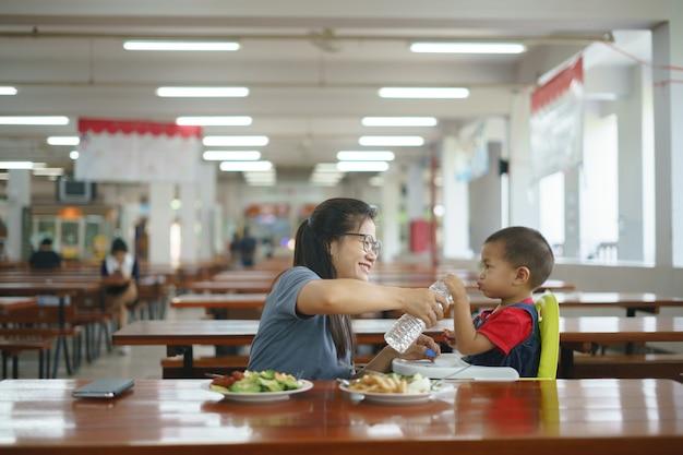 Ragazzo asiatico che mangia cibo alimentato da sua madre Foto Premium