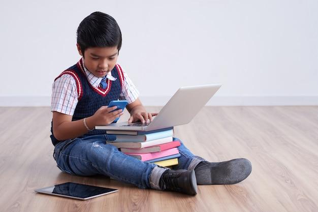 Ragazzo asiatico che si siede sul pavimento con la compressa e il computer portatile sui libri impilati e che per mezzo dello smartphone Foto Gratuite