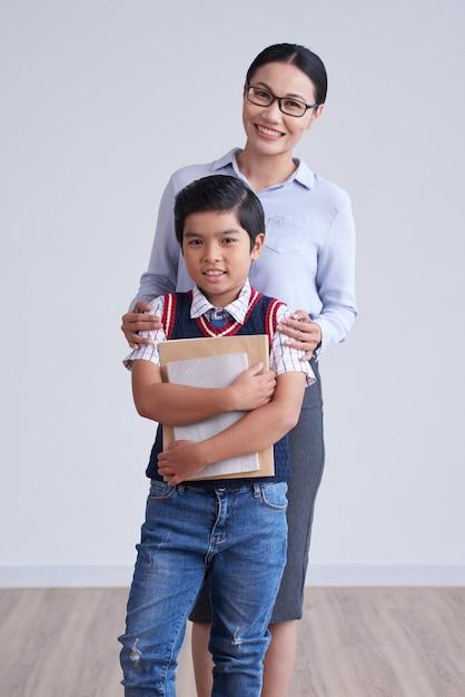 Ragazzo asiatico stringendo le carte e la donna con gli occhiali in piedi dietro con le mani sulle spalle Foto Gratuite