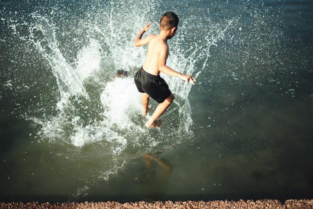 Ragazzo attivo che salta nell'acqua Foto Gratuite