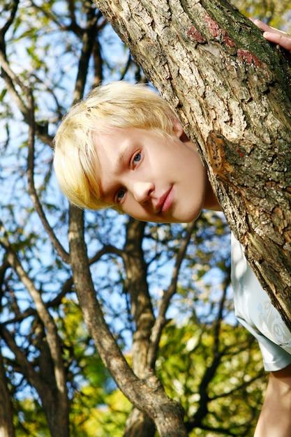 Ragazzo biondo attraente dietro un albero Foto Gratuite