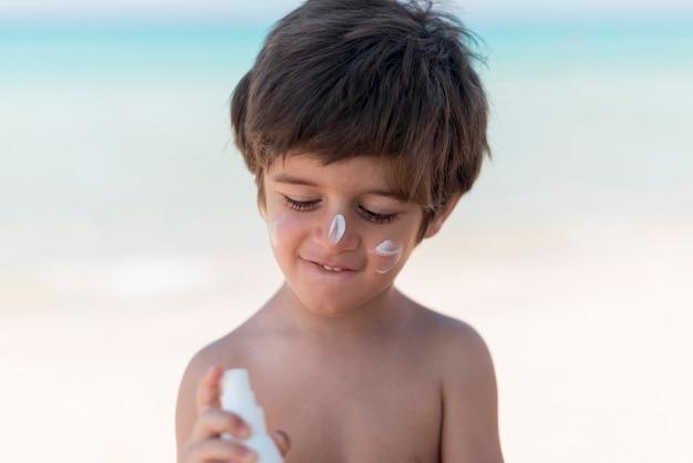 Ragazzo carino con crema solare in spiaggia Foto Gratuite