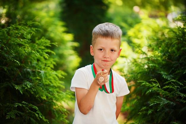 Ragazzo carino, tenendo e mostrando le medaglie annuncio sport day Foto Premium