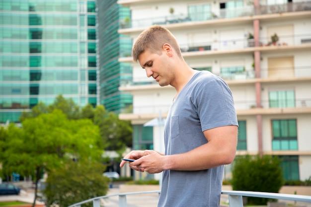 Ragazzo caucasico pensieroso che utilizza smartphone negli ambienti urbani Foto Gratuite