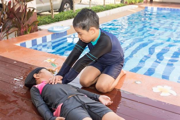 Ragazzo che aiuta annegando ragazza del bambino nella piscina facendo cpr. Foto Premium