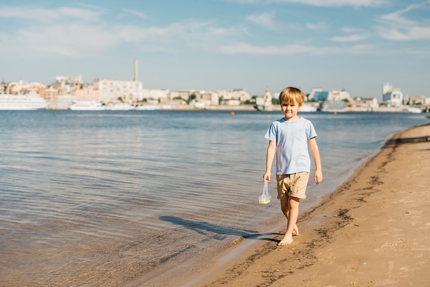 Ragazzo che cammina lungo la costa Foto Gratuite