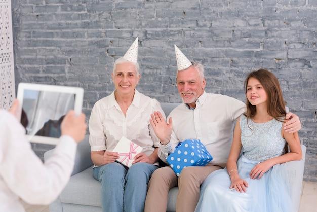 Ragazzo che cattura fotografia dei suoi nonni e sorella seduta sul divano con tavoletta digitale Foto Gratuite