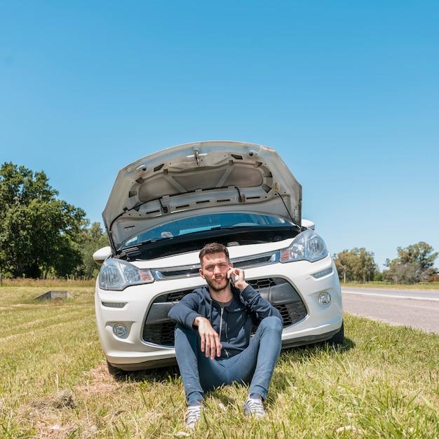 Ragazzo che chiama accanto all'automobile analizzata Foto Gratuite