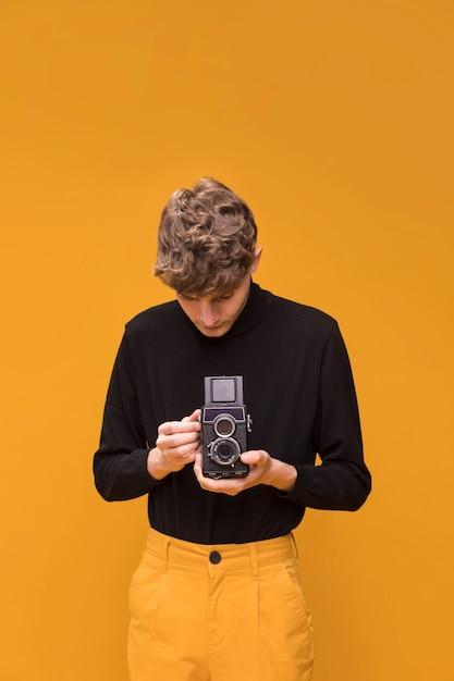 Ragazzo che filma con una videocamera in una scena gialla Foto Gratuite