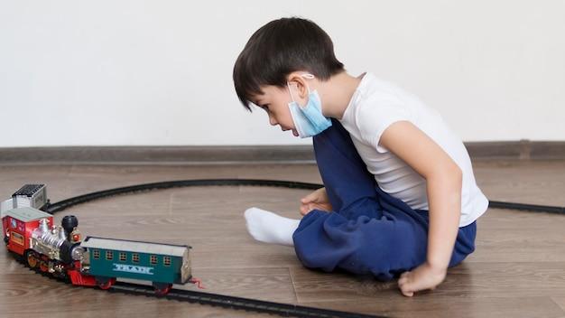 Ragazzo che gioca con il giocattolo del treno Foto Gratuite