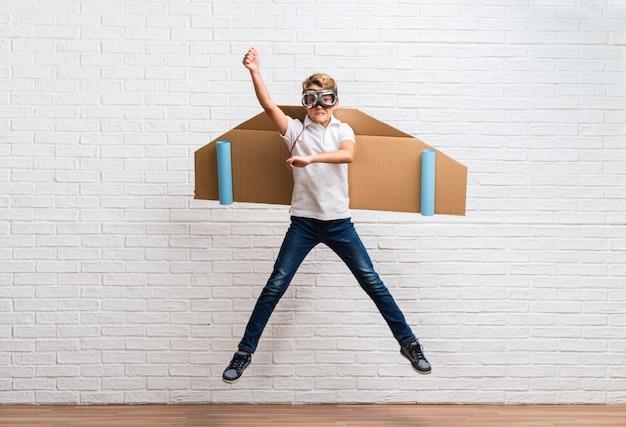 Ragazzo che gioca con le ali di aeroplano di cartone saltando Foto Premium