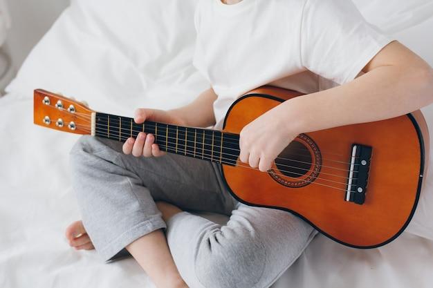 Ragazzo che gioca una piccola chitarra che si siede sul letto Foto Premium