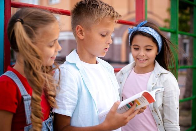 Ragazzo che legge da un libro con due ragazze Foto Gratuite