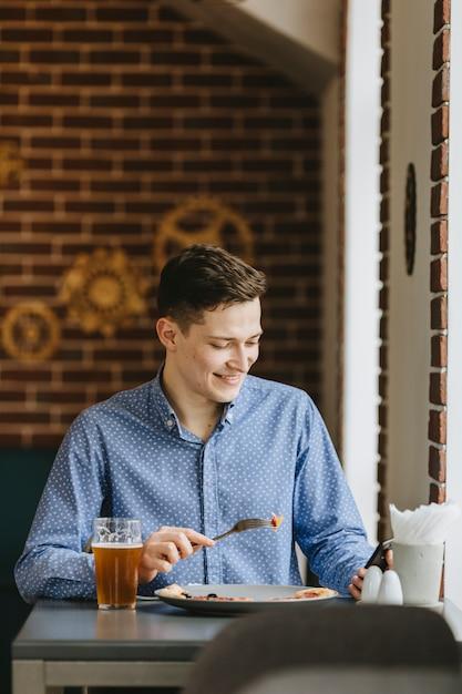 Ragazzo che mangia una birra in un ristorante Foto Gratuite