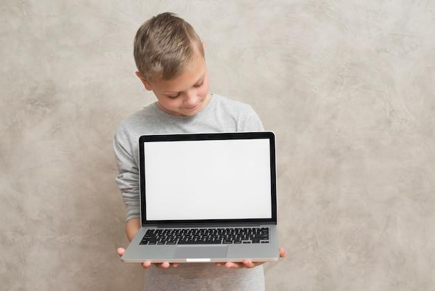 Ragazzo che presenta il modello di computer portatile Foto Gratuite